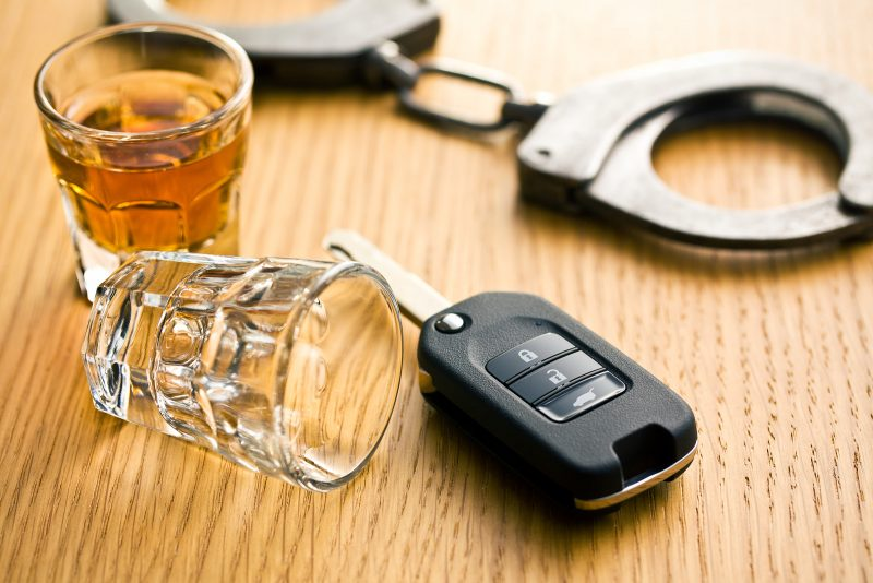 car keys and handcuffs beside alcohol