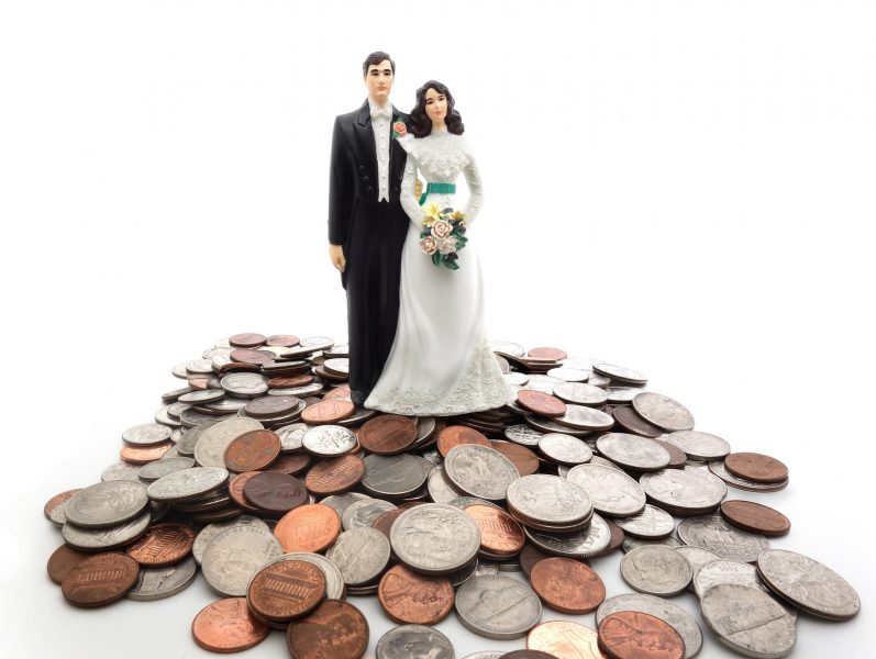 Couple cake topper sitting on top of cash